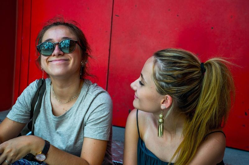 The Portraitist - 2017 EyeEm Awards Two People Girls Real People Sunglasses Togetherness Casual Clothing Happiness Friendship People Red Background Museo ABC Streetphotography Street Photography