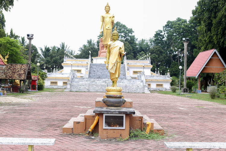 Wat Pikulthong Standing Buddha in Tumpat, Kelantan Sculpture Statue Human Representation Art And Craft Representation Architecture Male Likeness Built Structure Religion Day Creativity Tree Belief No People Spirituality Sky Nature Plant Place Of Worship Gold Colored Angel Budhism Budhist Temple Buddhist Temple