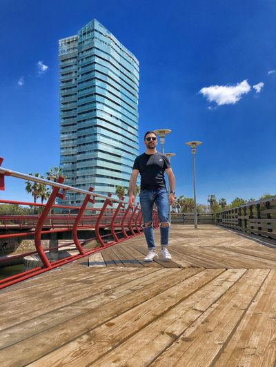 Full length of young man standing on footbridge in city against blue sky