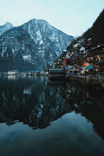 Houses by lake against mountain