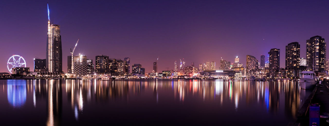 Illuminated buildings reflecting in river in city at night