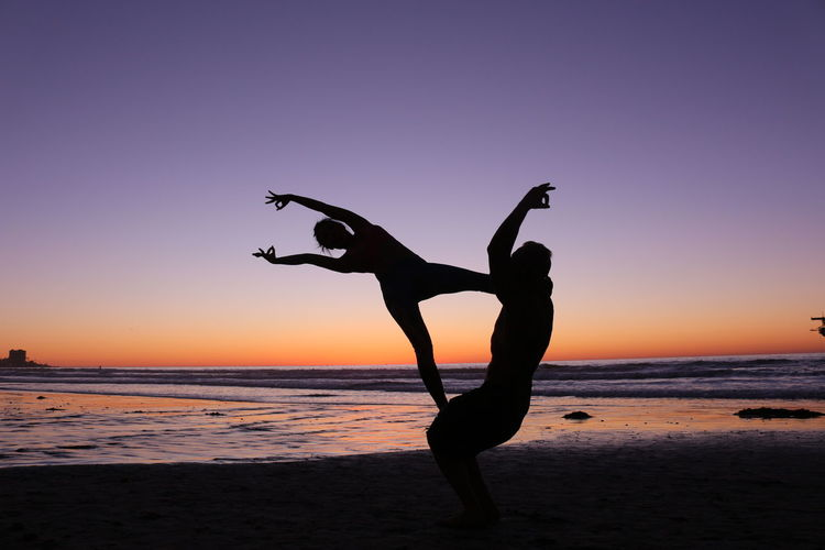 sunset silhouettes while balancing doing Acroyoga Well Balanced Concentrate Skills  Balance Acroyoga Sunset Acroyoga Chasing Sunsets Indescribable Colors Colors Of The Sky At Sunset Silhouette Sunset Horizon Over Water Scenics Sea Balance Beauty In Nature Clear Sky Flexibility Sky Beach Leisure Activity Skill  Outdoors Water Sand Lifestyles Handstand  Energetic Nature