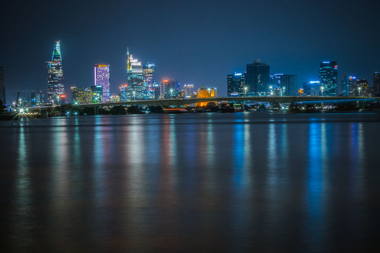 Illuminated cityscape by river against clear sky at night