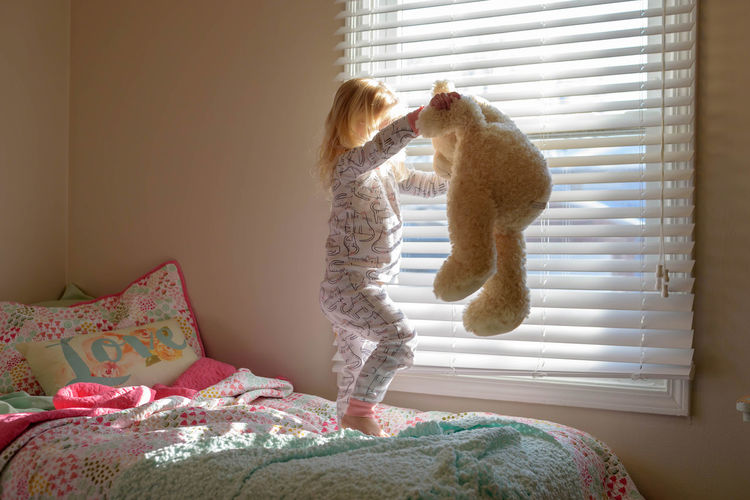 Cute blonde girl playing and dancing with teddy bear on her bed in early morning sunlight Bear Dancing Happy Morning Natural Light Bed Bedroom Childhood Childhood Memories Day Early Home Interior Indoors  Indoors  Interior Jumping Jumping On The Bed Little Girl Playing Rise And Shine Rise And Shine!  Stuffed Animal Teddy Bear