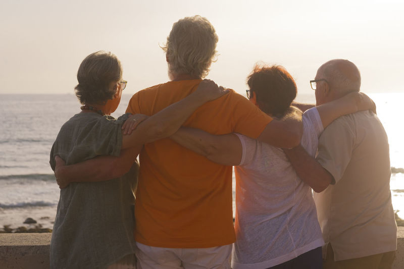 Friends with arms around looking at sea