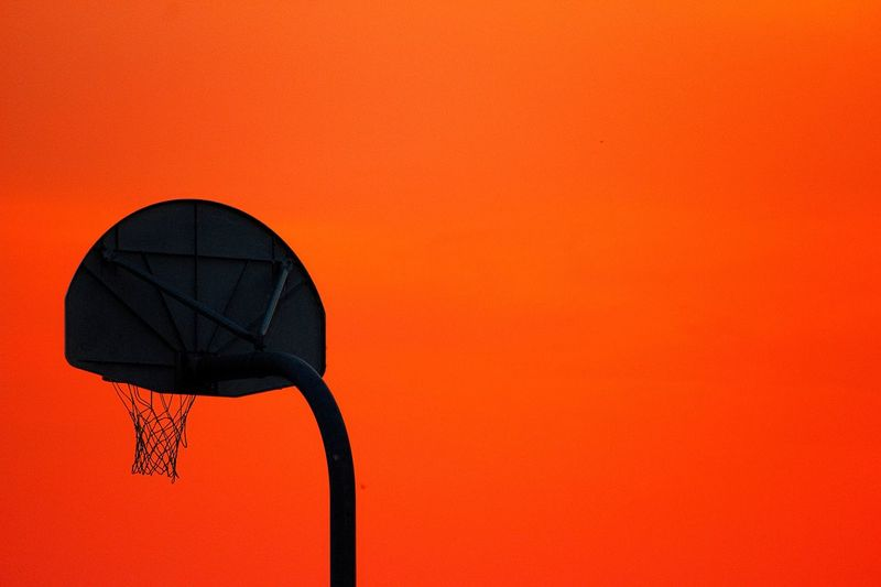 Low angle view of basketball hoop against clear sky during sunset