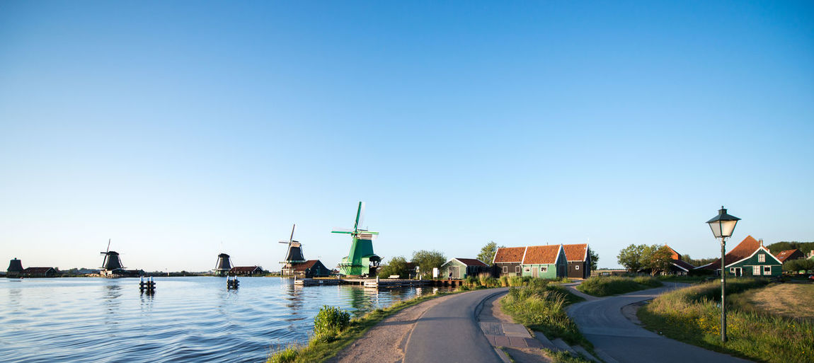 Empty roads and traditional windmills by canal against clear sky