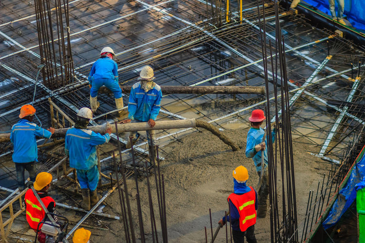 Construction workers are pouring concrete in post-tension flooring work. Mason workers carrying hose from concrete pump or also known as elephant hose during concreting work at construction site Construction Construction Equipment Construction Site Construction Machinery Flooring Post Tension Worker And Tools Worker In Action Adult Concrete Concrete Floor Concrete Pump Concrete Pumping Concreting Construction Area Construction Industry Construction Work Construction Worker Cooperation Coworker Elephant Hose Full Length Group Of People Hardhat  Hat Headwear Helmet High Angle View Industry Mason Mason Worker Masonry Mature Men Men Occupation People Post-tension Pouring Concrete Protection Protective Workwear Standing Teamwork Workers At Work Working