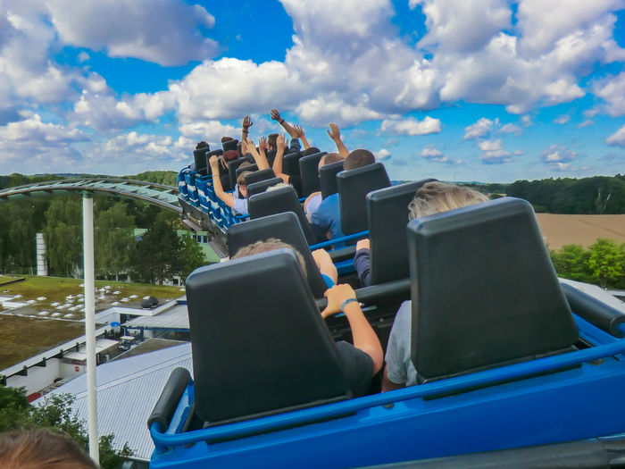 Rear View Of People Sitting In Rollercoaster Against Cloudy Sky