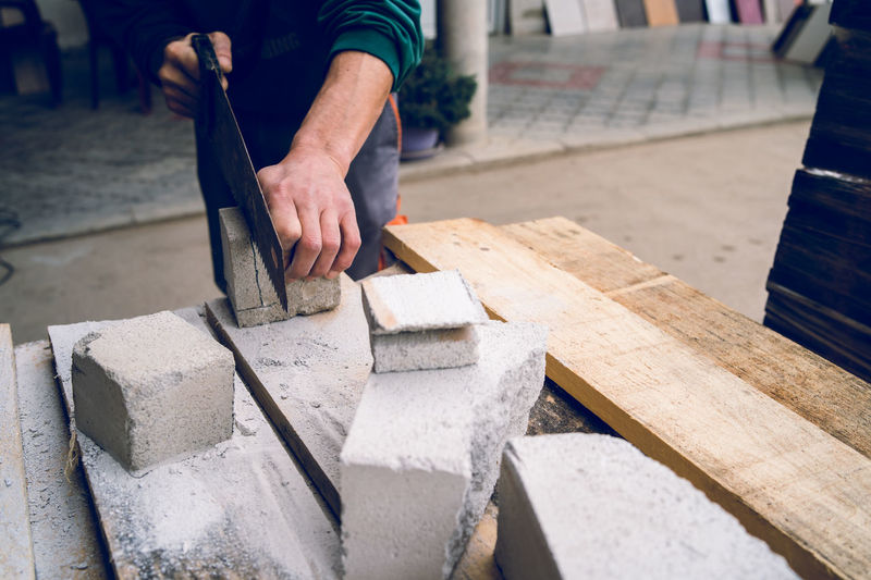 Cropped hands of man cutting concrete on table