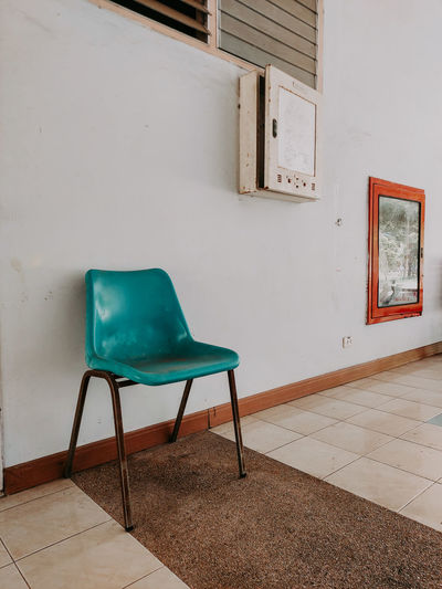 Empty chair against wall at home