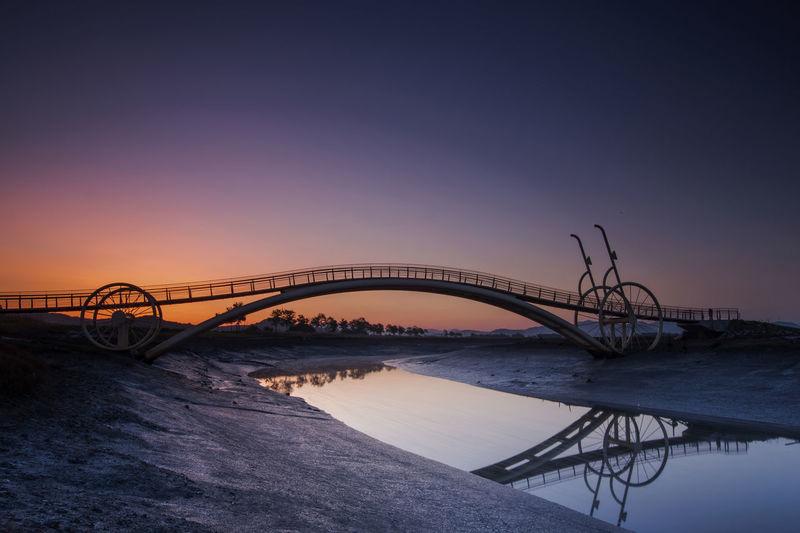 Bridge over river against sky during sunrise