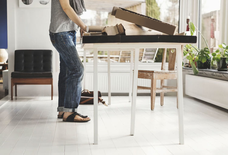 Low section of man standing on table at home