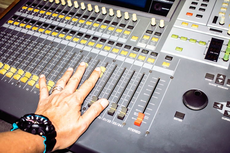 Cropped hand of man mixing music in recording studio