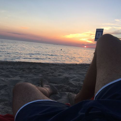 EyeEmNewHere See Two People Sea Real People Sunset Relaxation Lifestyles Wireless Technology Technology Low Section Leisure Activity Horizon Over Water Men Sitting Holding Nature Beach Human Leg Beauty In Nature Sky Outdoors