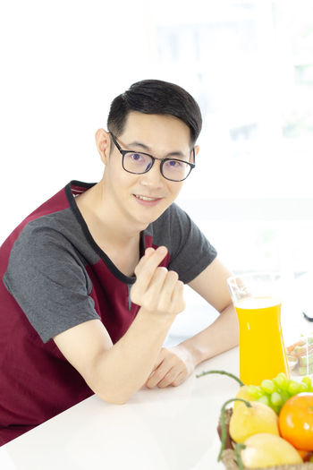 Portrait of smiling young man with drink on table