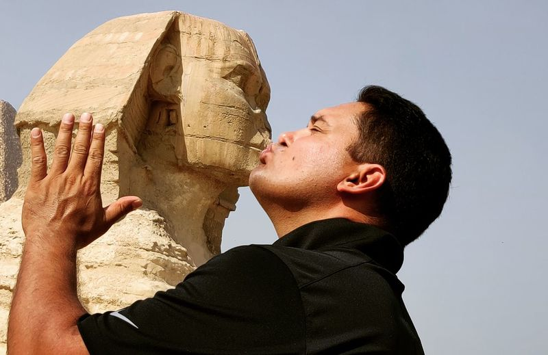 Optical illusion of man kissing giza pyramid