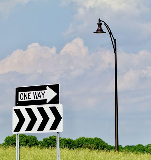 Road sign on street against sky