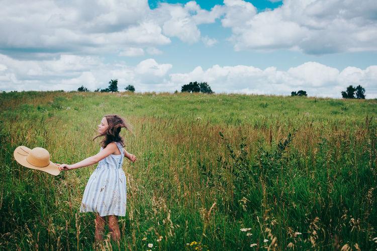 Girl in wildflower field against blue summer sky