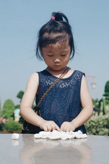 Girl with pebbles on table