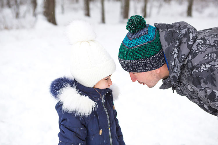 Dad and daughter look at each other closely in warm clothes, hats with a pompom on the stree