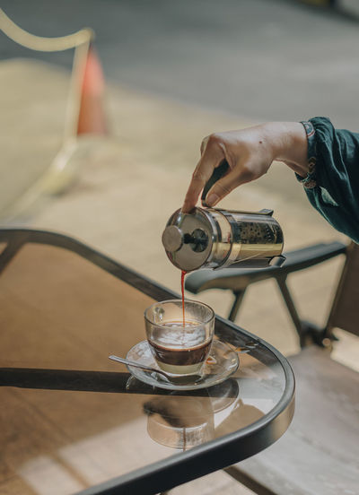 Cropped Hand Pouring Coffee In Cup At Table