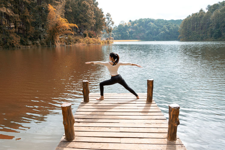 Rear view of woman practicing yoga while standing on pier over lake against trees