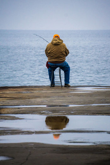 Carefree Escapism Fisherman Full Length Getting Away From It All Horizon Over Water Lake Leisure Activity Men Outdoors Real People Recreational Pursuit Reflection Showcase: January Water Wave Weekend Activities