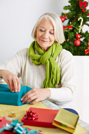 Smiling senior woman opening gift while sitting on table at home