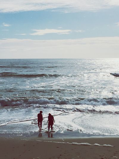Rear view of couple walking on shore at beach against sky
