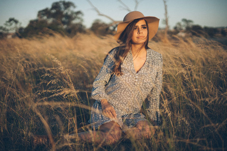 Thoughtful young woman wearing hat while sitting on grassy land during sunset