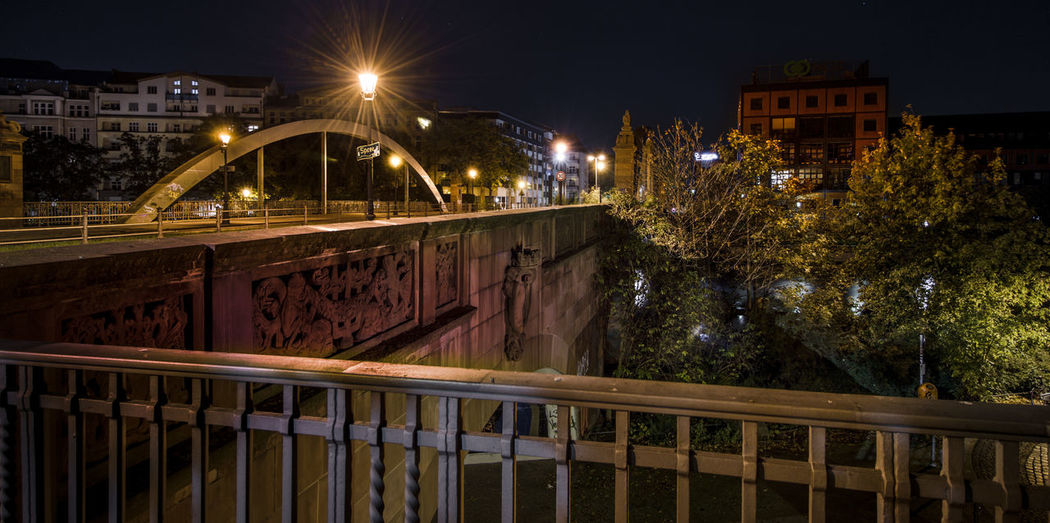 Illuminated bridge over canal by buildings in city at night