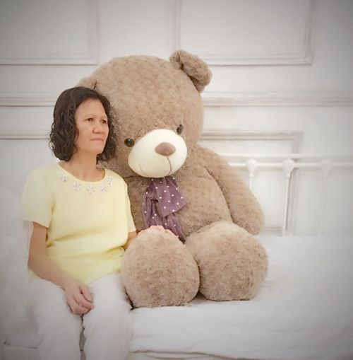 Woman With Large Teddy Bear Sitting On Bed At Home