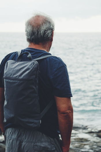 middle aged grey haired man wearing rucksack looking at the sea Sea View Tourist Travel Travelling Mature Adult Adult Man Rucksack Walking Adventure This Is Aging