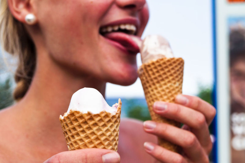 Midsection of woman licking ice cream