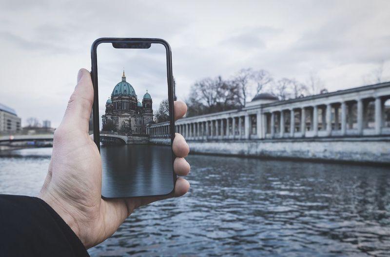 Man holding smart phone over river against sky