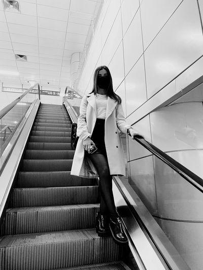 Full length of woman wearing mask standing on escalator