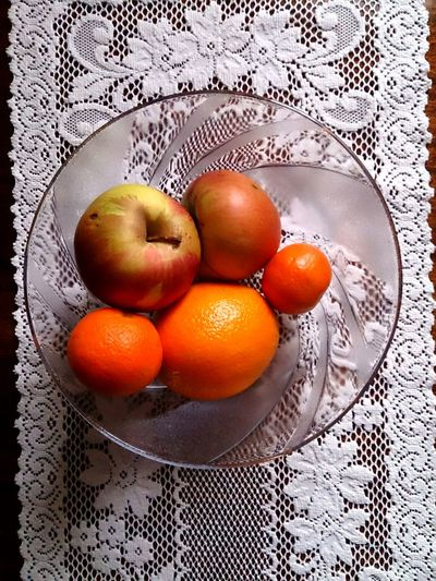 Fruit in bowl on lace cloth