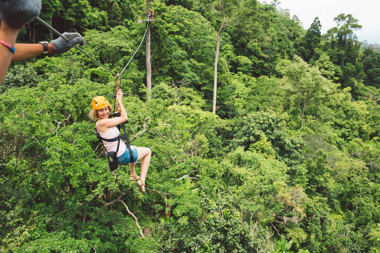 Full length of woman zip lining at forest
