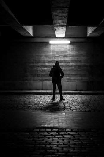 Rear View Of Man Standing Against Illuminated Wall At Night