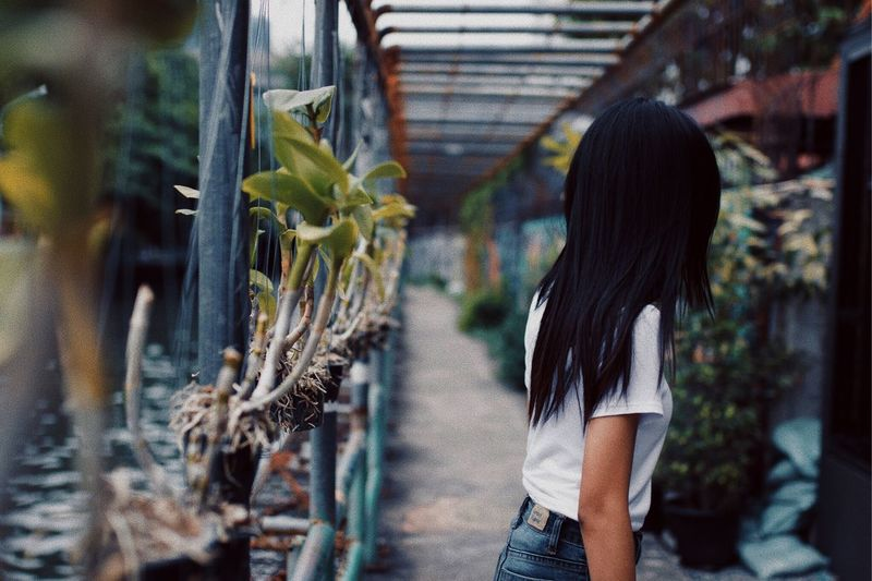 Side View Of Woman Standing By Plants In Greenhouse