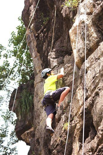 Low angle view of teenage boy climbing mountain