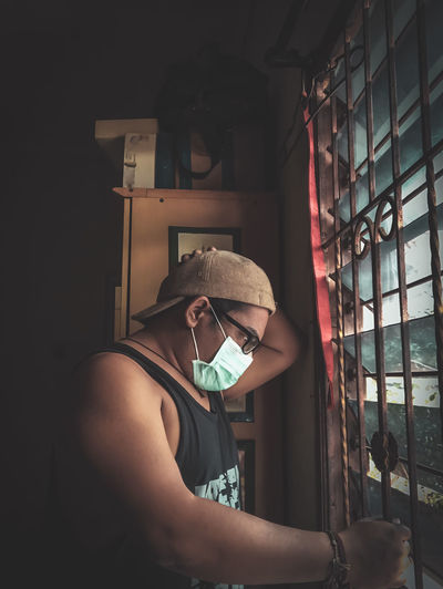 Side view of man wearing mask looking through window