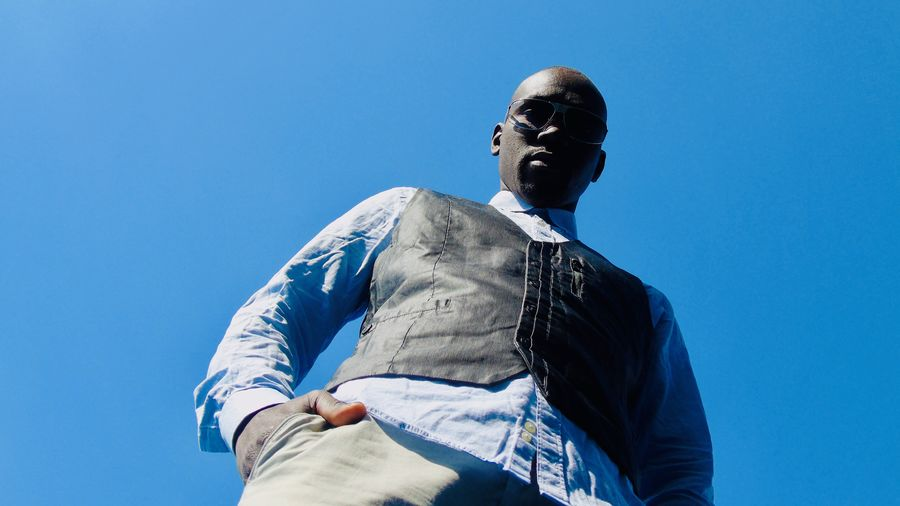 Low angle portrait of man standing against clear blue sky