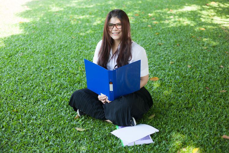 Portrait Of Young Woman With File And Papers Sitting On Grass