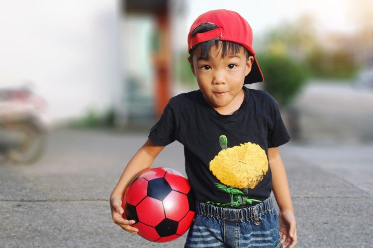 Portrait of happy boy holding ball while standing on footpath