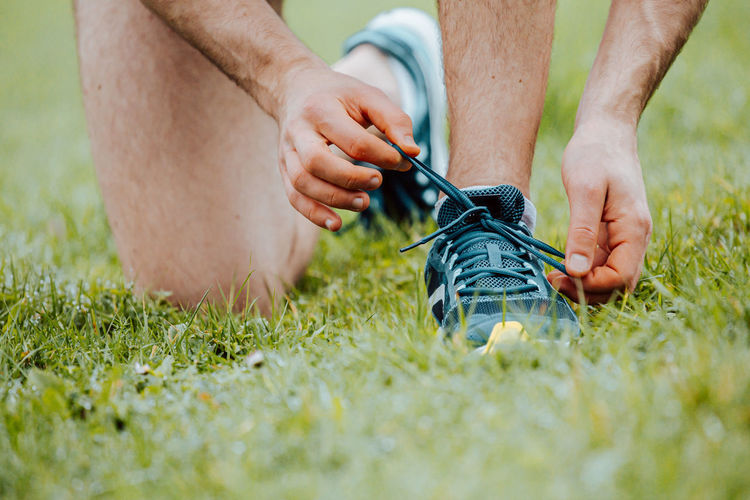 Low section of man tying shoelace outdoors