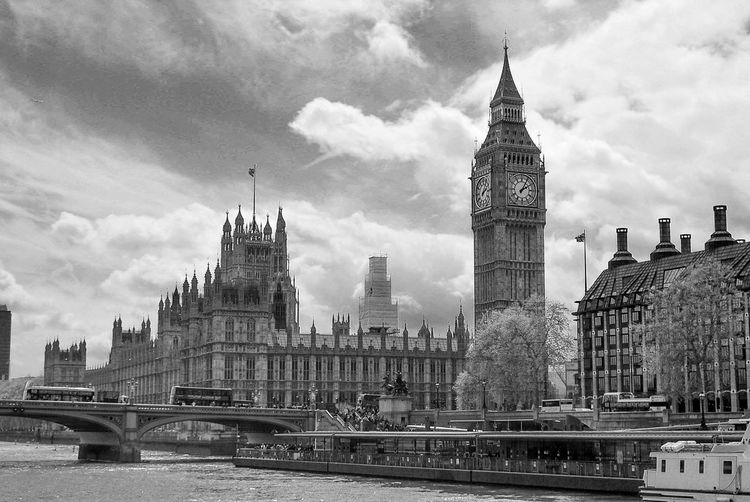 Thames river by houses of parliament and big ben against sky