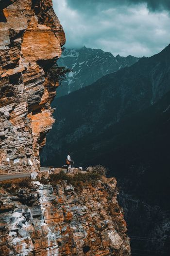 Hiker standing on cliff against mountains