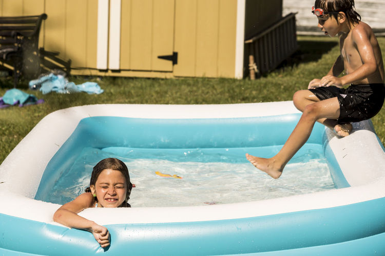 Playful Siblings In Wading Pool At Lawn